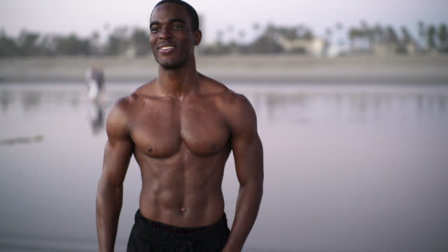 young black man, the well-trained muscular athlete, make body building exercise on the beach at sunset in santa monica, los angeles, california, usa - arm curl stock videos & royalty-free footage