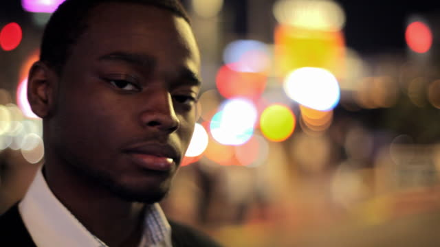 A young Black man wearing a collared white shirt stares intently at the camera.