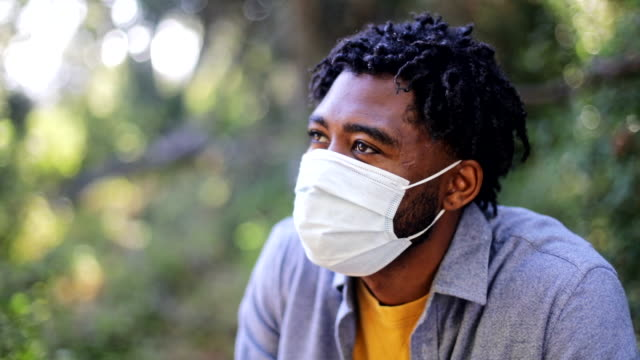 young black man wearing a face mask - sideways glance stock videos & royalty-free footage