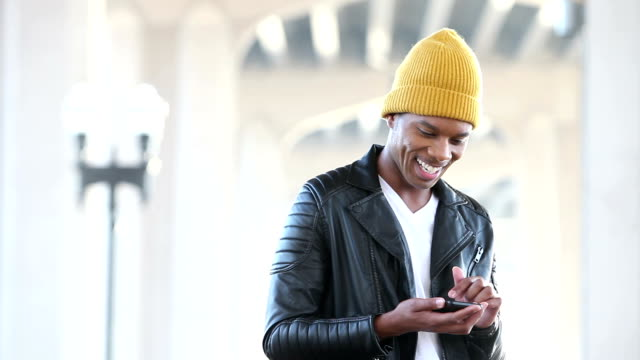 young black man wearing beanie looking at mobile phone - cool attitude stock videos & royalty-free footage