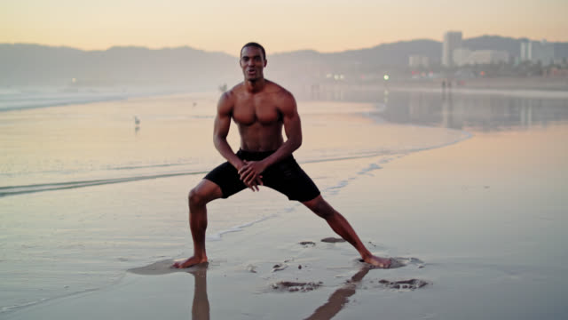 Young black man, well trained athlete, make side-step exercise on the beach at sunset in Santa Monica, California, USA