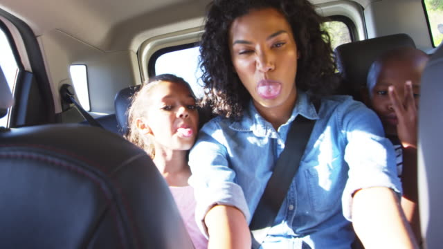 Young black mother taking photos with two children in a car