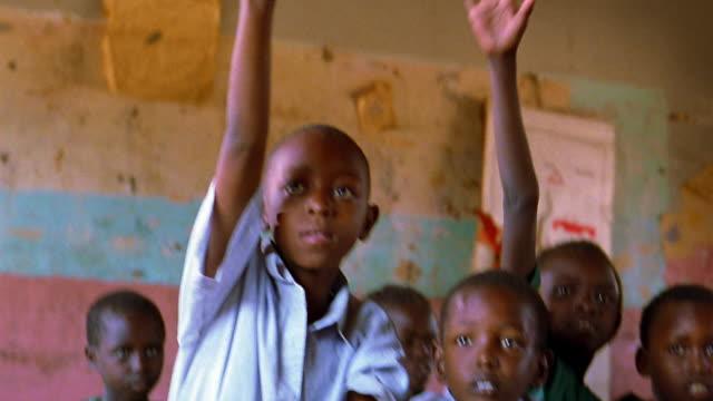 ms young black schoolchildren sitting at desks + excitedly raising hands / kenya - kenia stock-videos und b-roll-filmmaterial