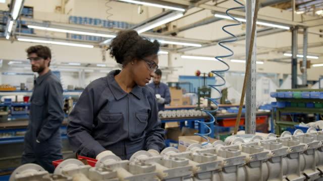 vidéos et rushes de jeune femme noire assemblant des pièces de rechange à une usine de pompe à eau à la ligne de production - en métal