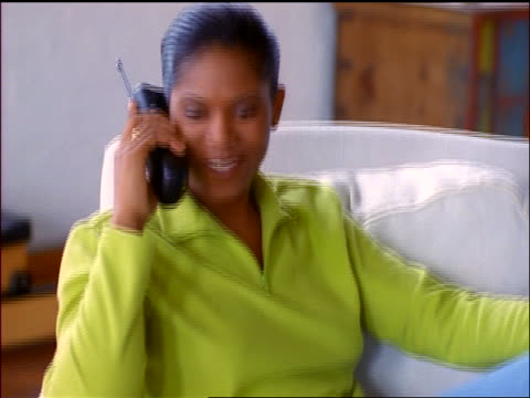 stockvideo's en b-roll-footage met young black woman in chair talks + laughs on cordless telephone - draadloze telefoon
