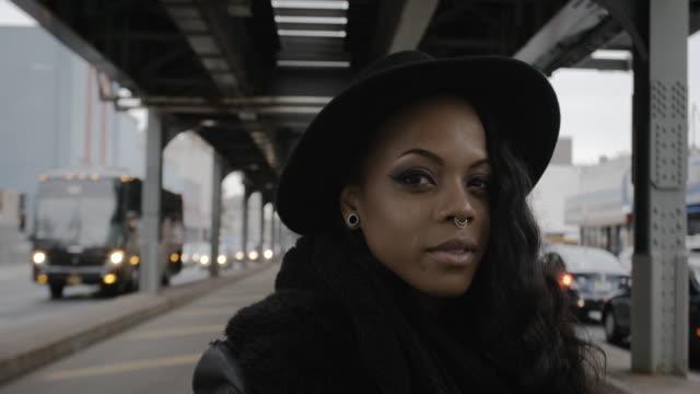 vídeos de stock, filmes e b-roll de a young, black woman in her twenties posing as a real person under the nyc subway - 4k - passagem subterrânea via pública