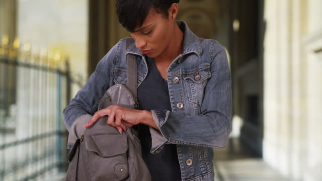 young black woman outdoors looking through purse for something - borsetta video stock e b–roll