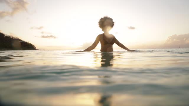 ls young black woman standing waist deep in ocean, feeling the water on her hands. - waist deep in water stock videos & royalty-free footage