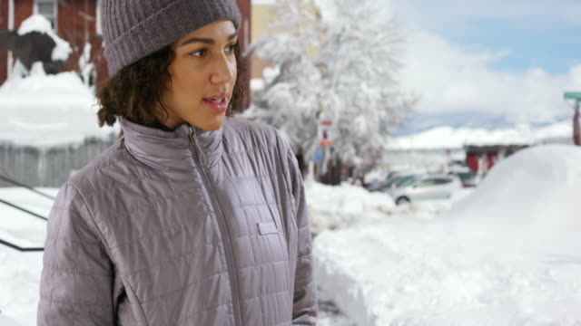 young black woman stands outside looking at fresh snowfall and smiling - winter coat stock videos & royalty-free footage