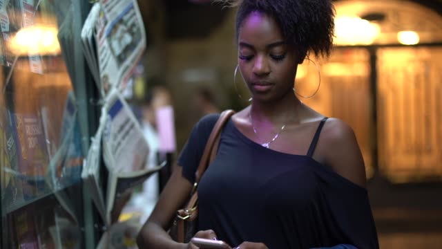 young black woman using mobile in the city at night - afro stock videos & royalty-free footage