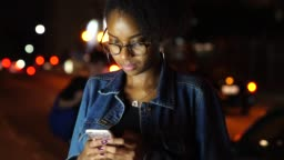 Young black woman using mobile in the city at night