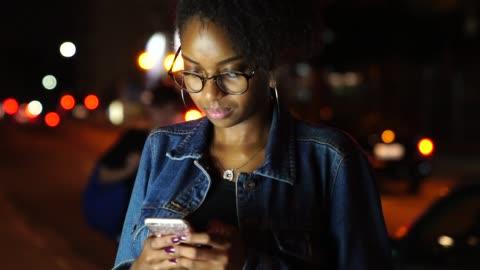 vídeos de stock, filmes e b-roll de jovem mulher negra usando móvel na cidade à noite - night
