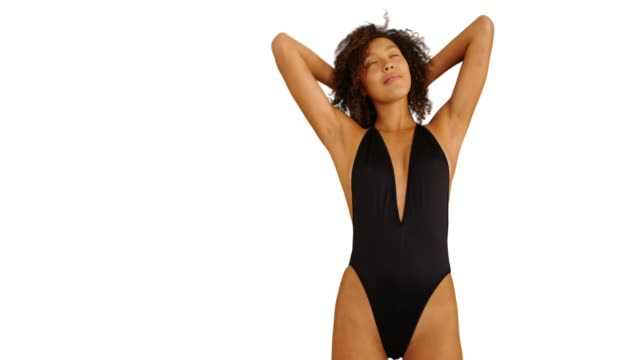 young black woman wearing swimsuit and standing on isolated background.  african woman on copyspace backdrop. 4k - 胴体点の映像素材/bロール