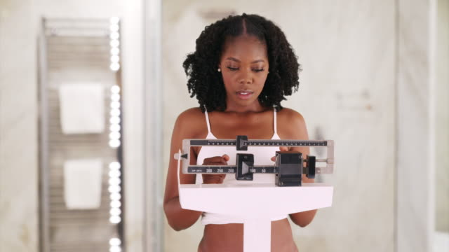 young black woman weighs herself on scale, frowning and shaking her head - slim stock videos & royalty-free footage