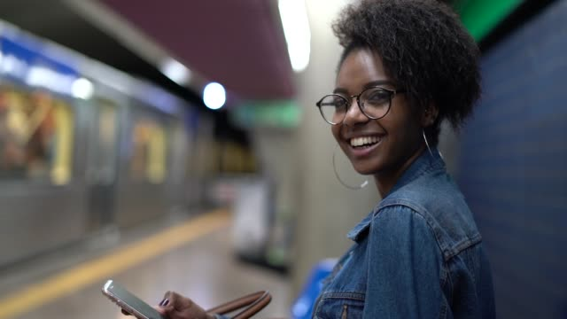 young black woman with afro hairstyle using mobile in the subway - são paulo stock videos & royalty-free footage
