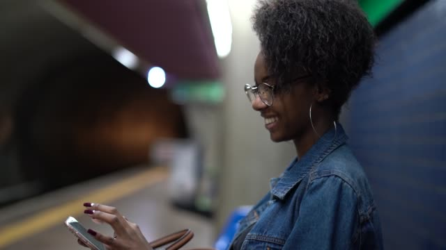 young black woman with afro hairstyle using mobile in the subway - casual clothing stock videos & royalty-free footage