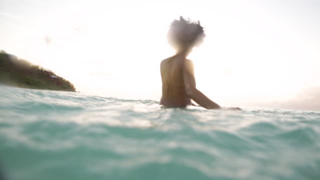 young black woman woman standing waist deep in ocean, splashing water with her hands. - waist deep in water stock videos & royalty-free footage