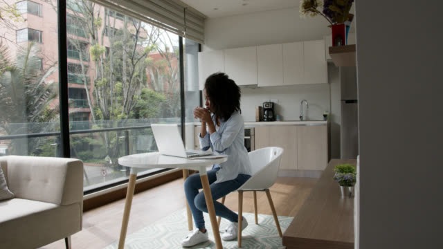 young black woman working from home with laptop and enjoying a cup of hot chocolate - tea hot drink stock videos & royalty-free footage