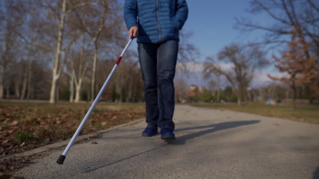 young blind man using his walking cane to be sure if there is no any obstacle on his way - visual impairment stock videos & royalty-free footage