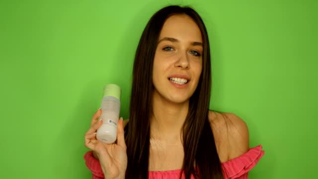 vídeos de stock, filmes e b-roll de jovem blogueira no fundo verde apresentar cosméticos de beleza enquanto se senta na câmera frontal - blogar