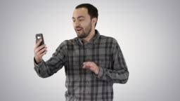 Young blogger recording video on his phone while walking on gradient background