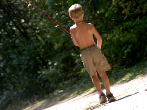 CANTED REAR VIEW young blond boy carrying fishing rod walking on dirt road in forest