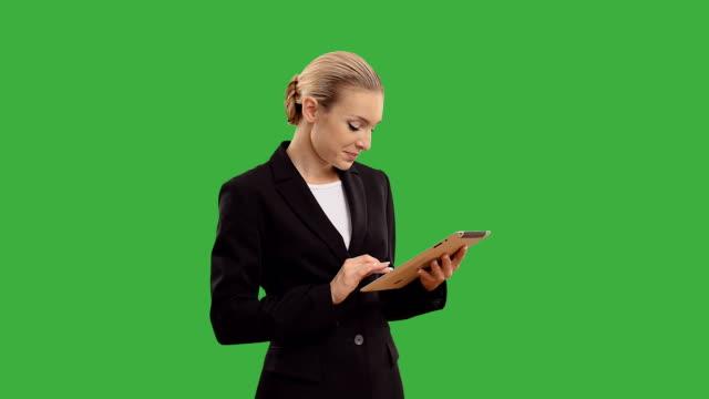jungen blonden geschäftsfrau sprechen sie mit einem tablet-pc auf grünen bildschirm. - geschäftsfrau stock-videos und b-roll-filmmaterial