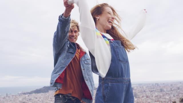 junge blonde paare tanzen am aussichtspunkt - barcelona spanien stock-videos und b-roll-filmmaterial