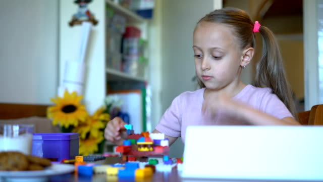 Young blond girl playing with plastic blocks at home