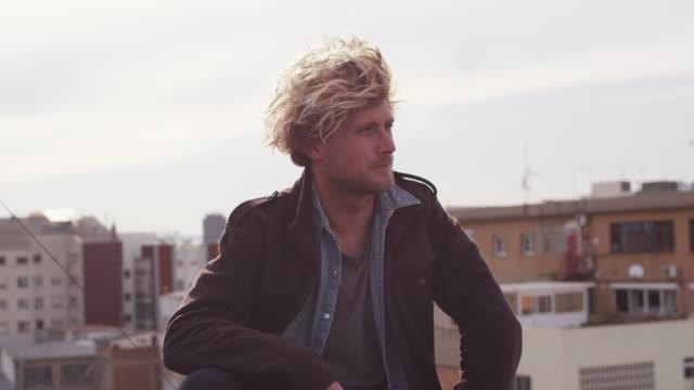 junge blonde mann am bau terrasse sitzen - 25 29 jahre stock-videos und b-roll-filmmaterial