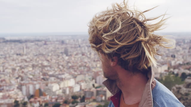 young blond male tourist looking at cityscape - denim jacket stock videos and b-roll footage