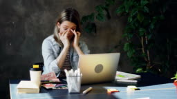 Young blond woman is sitting in office working with computer. She is tired so she is touching her face and hair, rubbing her eyes, stretching her neck after long day at work.