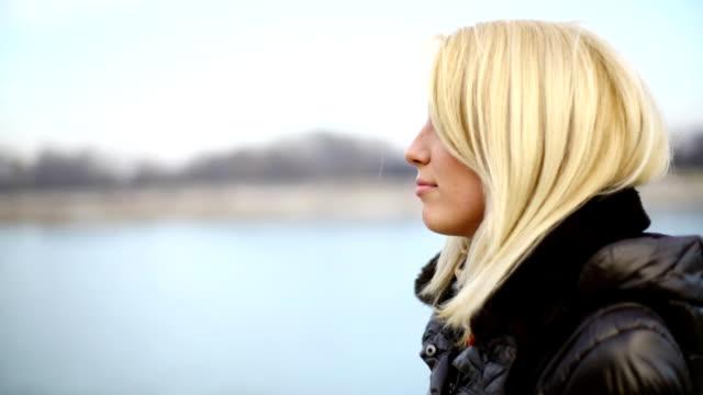 若い金髪女性、川に沿って歩くます。