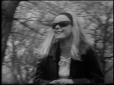 vídeos de stock, filmes e b-roll de b/w 1967 young blonde female hippie in sunglasses headband smiling walking at bein / detroit - abuso de substâncias