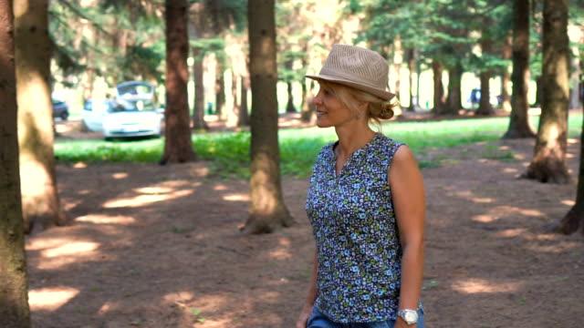 vídeos y material grabado en eventos de stock de joven mujer rubia relajado andando y disfrutando de su tiempo en el bosque. - espalda humana