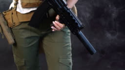 Young blonde female shred in military outfit with assault rifle in studio