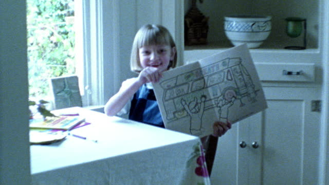 blue overexposed young blonde girl coloring at table holds up coloring book to camera - overexposed video stock e b–roll