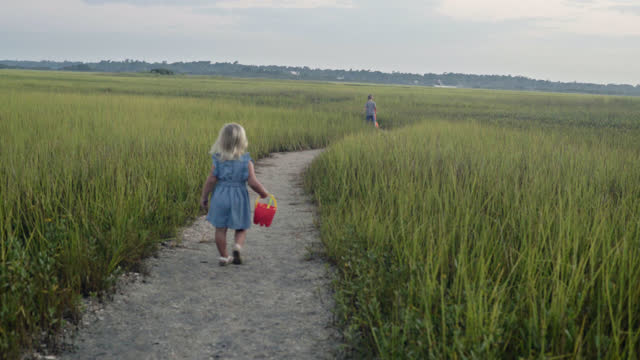 Young blonde girl follows brother through coastal marsh with sand toys at dawn.