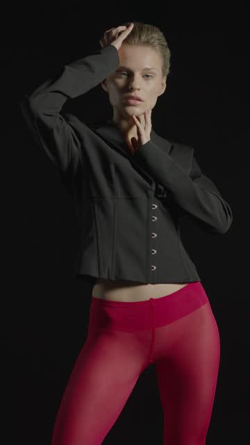 黒いジャケットと赤いパンストを着た若いブロンドの女の子が彼女の手で彼女の顔に触れ、ゆっくりと動きます。 - タイツ点の映像素材/bロール