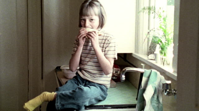 OVEREXPOSED young blonde girl sitting on kitchen counter eating sandwich + giggling
