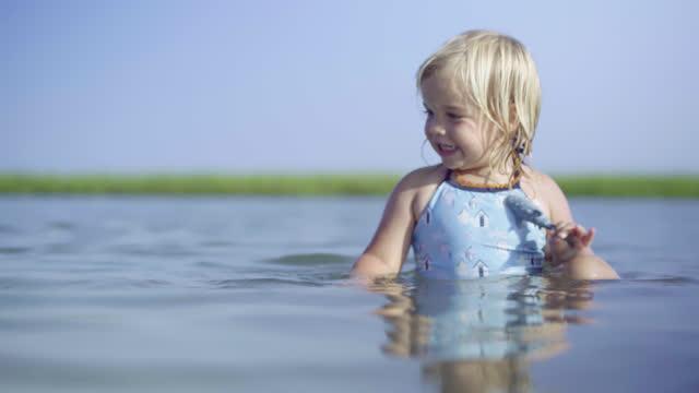 vídeos de stock e filmes b-roll de young blonde girl swims, splashes and plays in coastal tide pool. - nostalgia