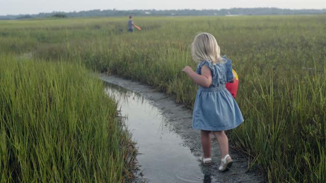 young blonde girl walks carefully behind brother through coastal marsh with red bucket at dawn. - badbyxor bildbanksvideor och videomaterial från bakom kulisserna