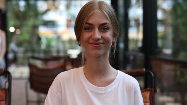 vidéos et rushes de jeune femme blonde créatrice souriant à l'appareil-photo dans le café, la tête et les épaules - la vingtaine