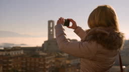 Young blonde woman dressed for winter using a smart phone to take a picture of an italian panorama with old houses and hills on a sunny day
