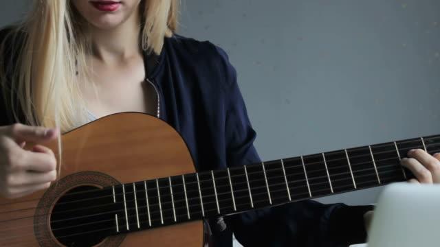 Jeune femme blonde, jouer de la guitare à l'aide de son ordinateur portable