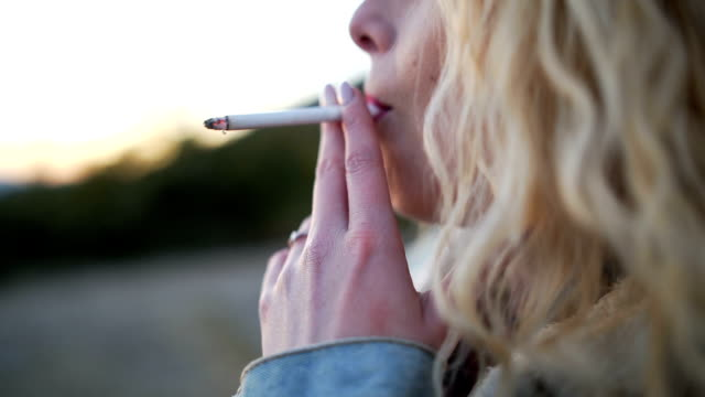 young blonde woman smoking cigarette outdoors - cigarette stock videos & royalty-free footage