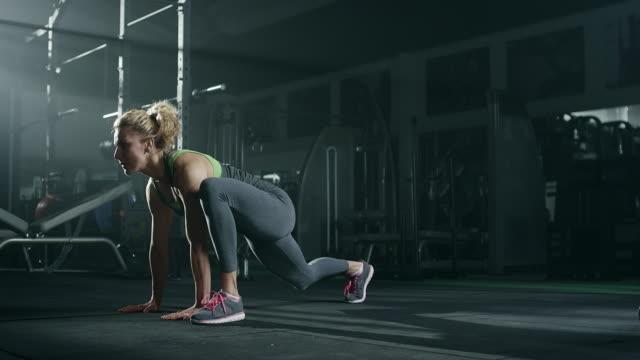 unga blonda kvinnan stretching i gymmet - böja sig bildbanksvideor och videomaterial från bakom kulisserna