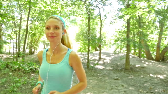 young blonde woman using headphones during run on dirt path - hair accessory stock videos & royalty-free footage
