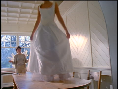 vídeos de stock e filmes b-roll de young blonde woman walking on dining room table modelling wedding dress for mother - 1990