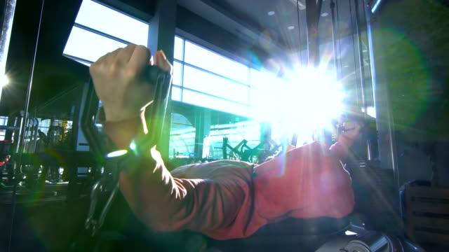 vídeos y material grabado en eventos de stock de young body builder ejercicio en cable crossover - press de banca